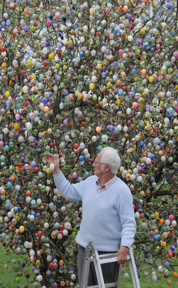 FILE - The April 11, 2011 file photo shows Volker Kraft decorating a tree with 9,800 Easter eggs at the garden of pensioner couple Christa and Volker Kraft in Saalfeld, Germany. Volker Kraft's apple sapling sported just 18 eggs when he first decorated it for Easter. Four decades later, the sturdy tree is festooned with 9,800 eggs, artfully decorated with everything from beads to sea shells.  (AP Photo/Jens Meyer, file)