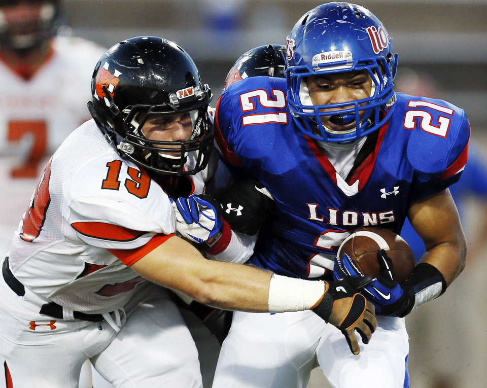 Photo - Moore's Ryan Lujan (21) is stopped by Norman's Michael Beard (19) during a high school football game between Moore and Norman in Moore, Okla., Thursday, Sept. 6, 2012. Photo by Nate Billings, The Oklahoman