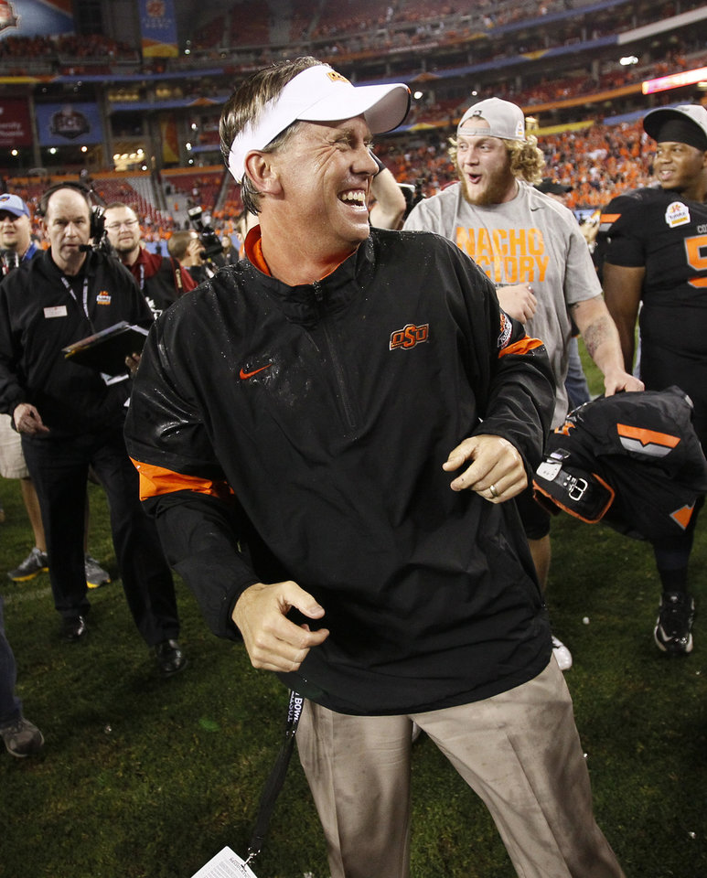 Photo - Oklahoma State head coach Mike Gundy smiles with his players after winning the Fiesta Bowl NCAA college football game against Stanford, Monday, Jan. 2, 2012, in Glendale, Ariz. Oklahoma State won 41-38 in overtime. (AP Photo/Matt York)  ORG XMIT: PNP145