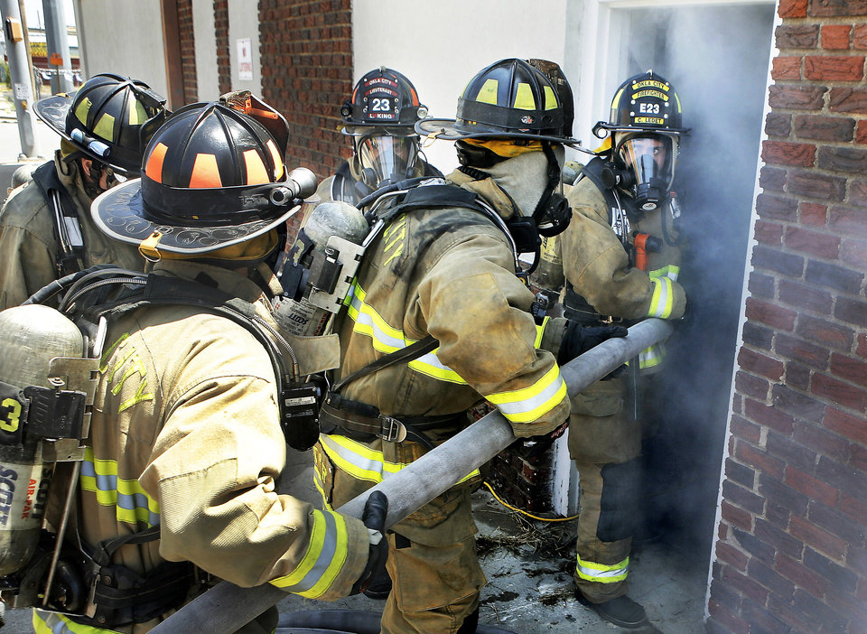 Photo - Oklahoma City firefighters prepare to enter a smoke-filled vacant building during a training exercise.