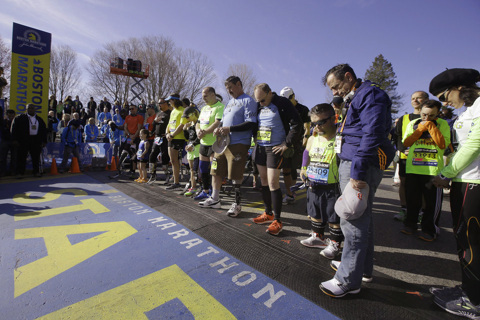 Photo - Mobility-impaired runners gather at the start line for a moment of silence before the 118th Boston Marathon Monday, April 21, 2014 in Hopkinton, Mass. (AP Photo/Stephan Savoia)