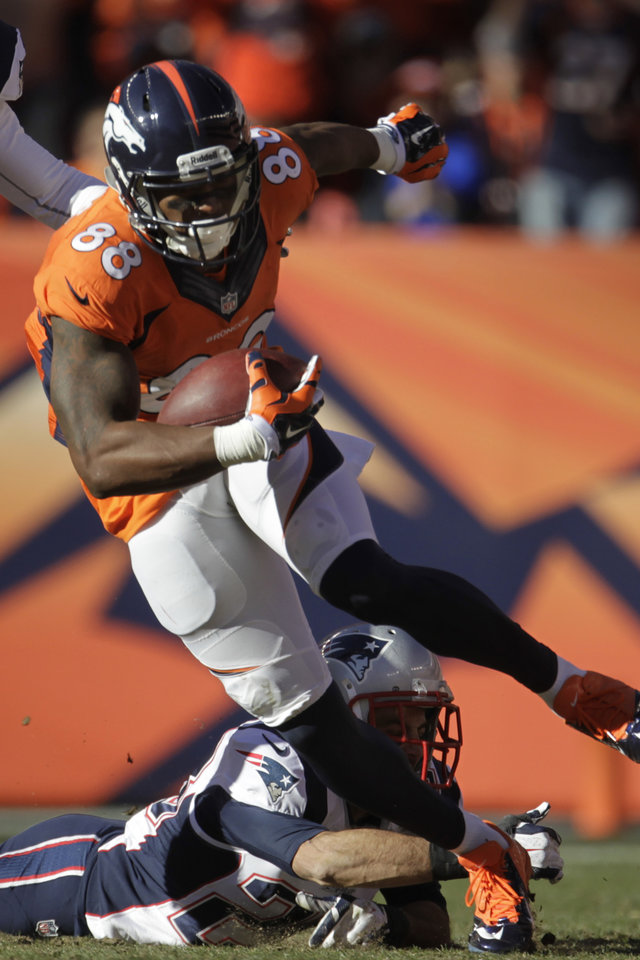 Photo - Denver Broncos wide receiver Demaryius Thomas (88) breaks a tackle from New England Patriots strong safety Steve Gregory (28) during the first half of the AFC Championship NFL playoff football game in Denver, Sunday, Jan. 19, 2014. (AP Photo/Joe Mahoney)