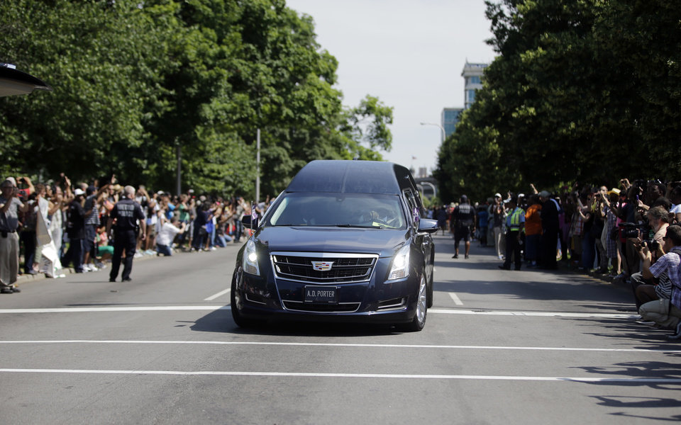 Photo - Crowds line the route of the procession led by the hearse carrying the body of Muhammad Ali, Friday, June 10, 2016, in Louisville, Ky. (AP Photo/Darron Cummings)