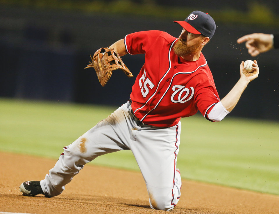 Photo - Washington Nationals first baseman Adam LaRoche throws out San Diego Padres' Jace Peterson at first after making a diving stop along the foul line during the fourth inning of a baseball game Saturday, June 7, 2014, in San Diego. (AP Photo/Lenny Ignelzi)
