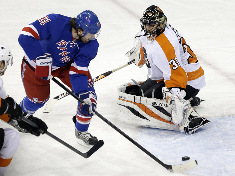 Photo - New York Rangers' Rick Nash (61) skates past Philadelphia Flyers goalie Ilya Bryzgalov (30), of Russia, to score a goal during the third period of an NHL hockey game Tuesday, March 5, 2013, in New York. The Rangers won the game 4-2. (AP Photo/Frank Franklin II)