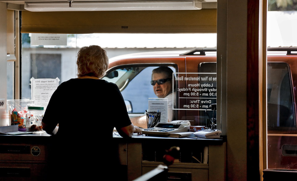 Photo - Bank teller Mary Graves helps a customer in the drive thru at First State Bank on Friday, Aug. 23, 2013 in Elmore City, Okla. The bank established in 1903 is the smallest bank in the state of Oklahoma with $9.5 million in total assets. The home town bank operates with seven employees, and has about 1000 customers in Elmore City that is home to more than 650 residents.   Photo by Chris Landsberger, The Oklahoman