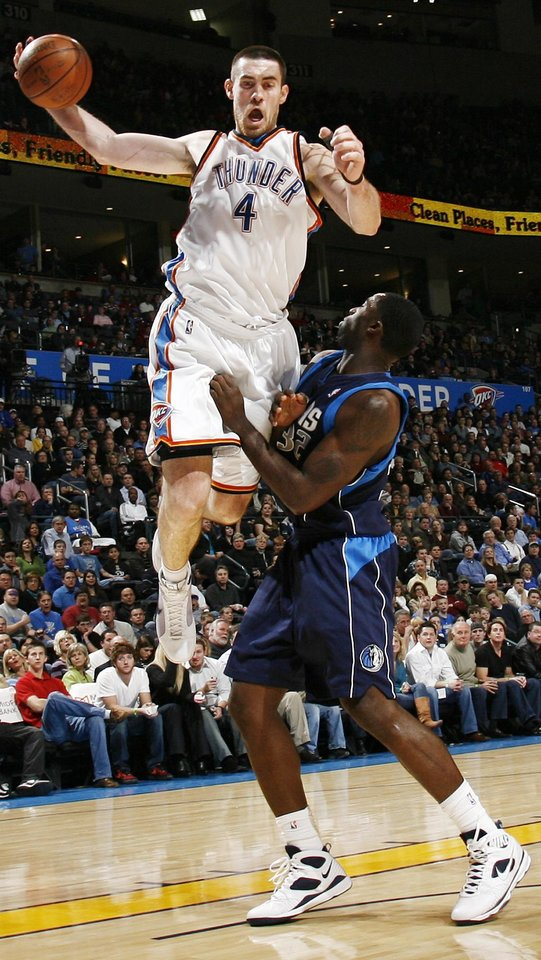 Oklahoma City's Nick Collison (4) grabs a rebound over Brandon Bass (32) fo Dallas in the first half during the NBA basketball game between the Dallas Mavericks and the Oklahoma City Thunder at the Ford Center in Oklahoma City, March 2, 2009. BY NATE BILLINGS, THE OKLAHOMAN