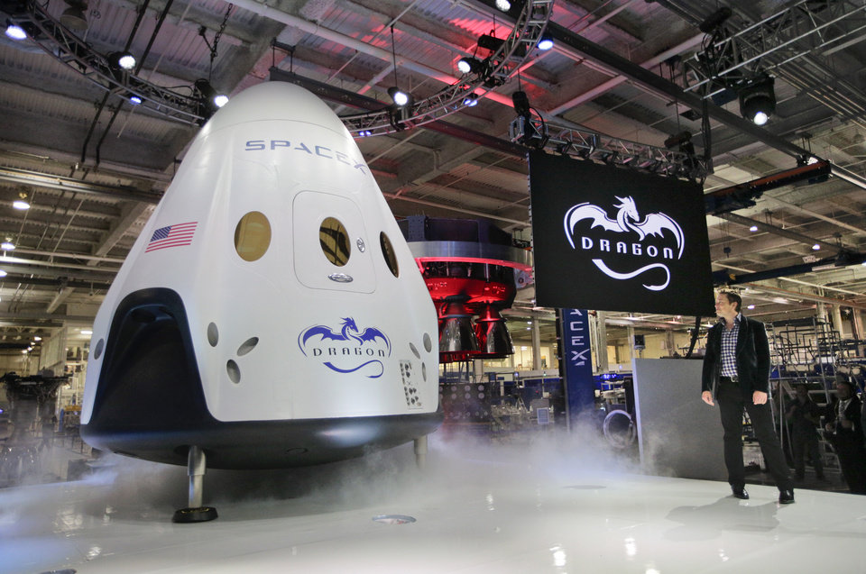 Photo - Elon Musk, right, unveils the SpaceX Dragon V2 spacecraft Thursday, May 29, 2014, in Hawthorne, Calif. SpaceX, which has flown unmanned cargo capsules to the International Space Station, unveiled the new spacecraft Thursday designed to ferry up to seven astronauts to the space station. (AP Photo/Jae C. Hong)