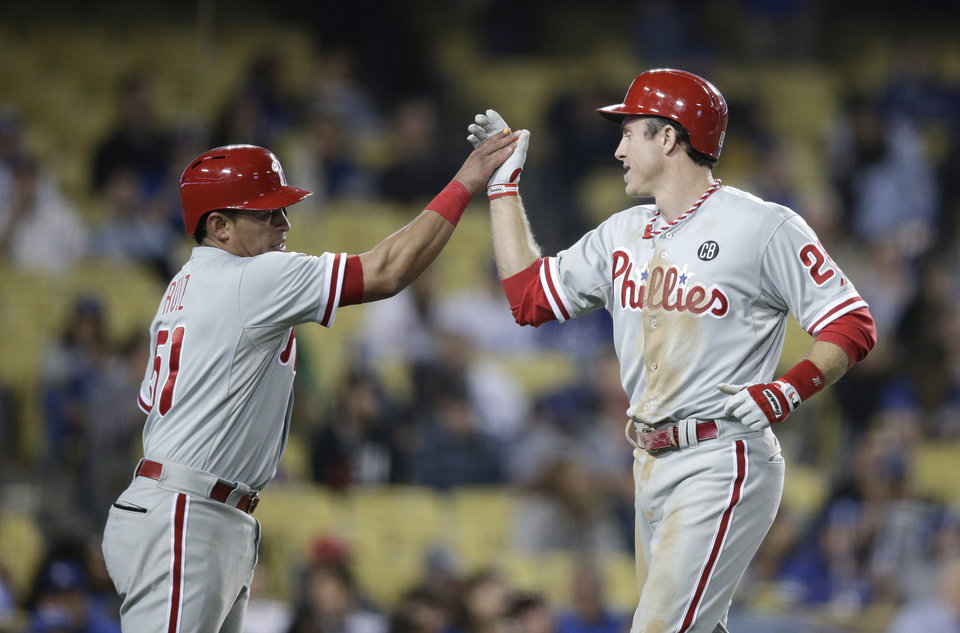Photo - Philadelphia Phillies' Chase Utley, right, and Carlos Ruiz celebrate after they scored on a single hit by Marlon Byrd during the ninth inning of a baseball game against the Los Angeles Dodgers on Thursday, April 24, 2014, in Los Angeles. (AP Photo/Jae C. Hong)