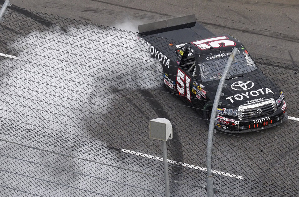 Photo -   Denny Hamlin (11) does a burnout as he celebrates winning the NASCAR truck race at the Martinsville Speedway in Martinsville, Va. Saturday, Oct. 27, 2012. (AP Photo/Steve Sheppard)
