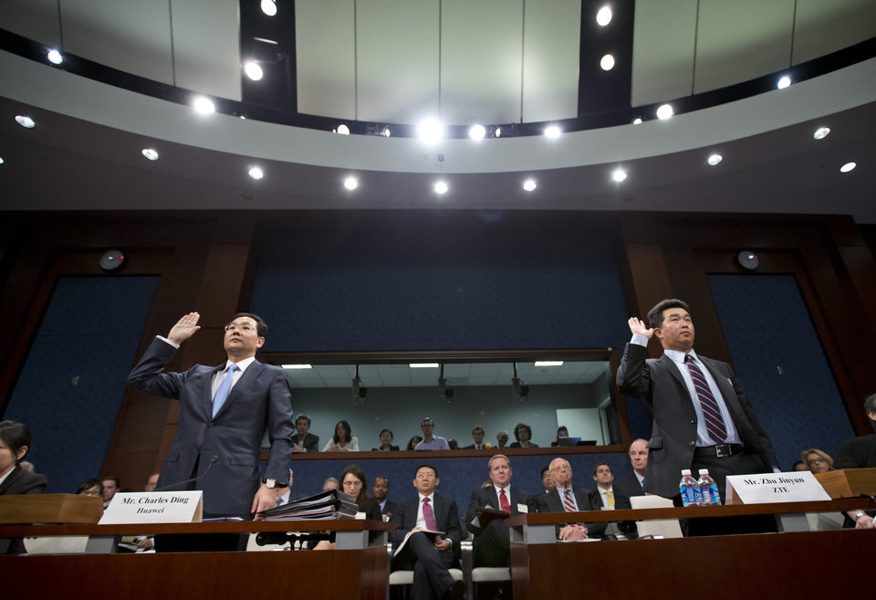 Photo -   Executives of two major Chinese technology companies, Charles Ding, Huawei Technologies Ltd senior vice president for the U.S., left, and Zhu Jinyun, ZTE Corporation senior vice president for North America and Europe, are sworn in on Capitol Hill in Washington, Thursday, Sept. 13, 2012, prior to testifying before the House Intelligence Committee as lawmakers probe whether their expansion in the U.S. market poses a threat to national security. (AP Photo/J. Scott Applewhite)