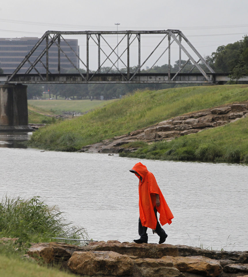 Photo - Marvin Helms goes to get some of his equipment as he fishes on the Trinity River in Fort Worth, Texas as rain falls in the area on Thursday, July 17, 2014. (AP Photo/Fort Worth Star-Telegram, Rodger Mallison)