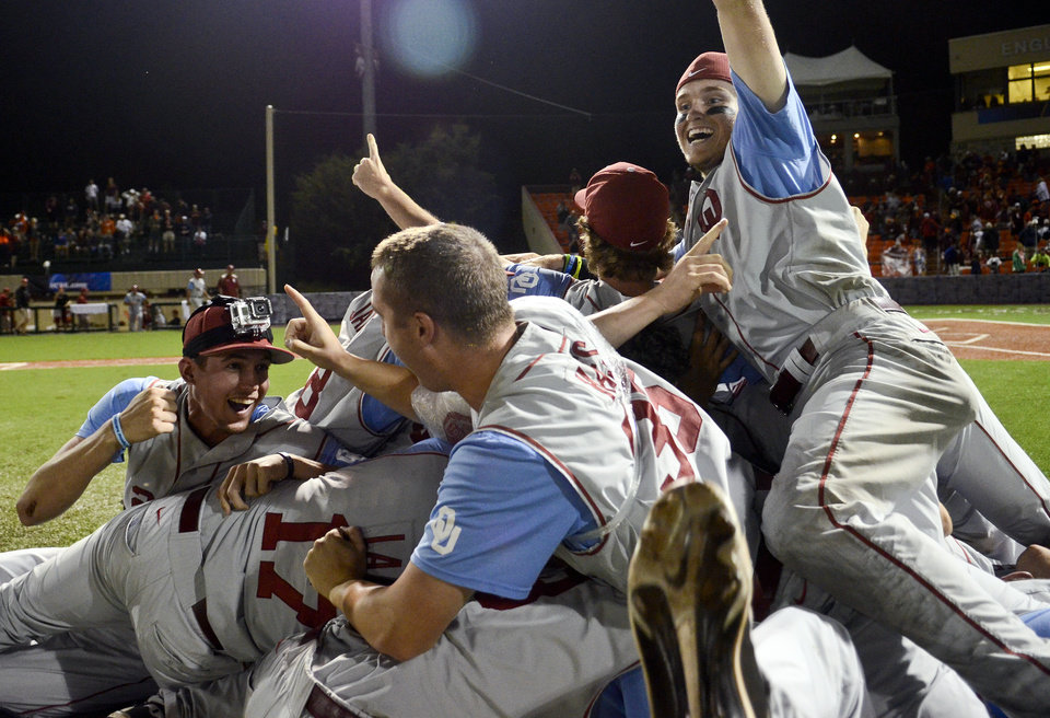 Oklahoma's Dusty Dishman, left, Kyle Hayes, center, and Craig Aikin, right, celebrate with teammates following an NCAA college baseball tournament regional game at English Field in Blacksburg, Va., Sunday, June 2, 2013. Oklahoma won 10-4. (AP Photo/Michael Shroyer) ORG XMIT: VAMS163
