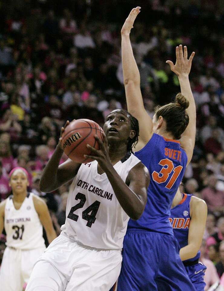 Photo - South Carolina's Aleighsa Welch (24) gets past Florida's Lily Svete as she drives for the basket during the second half of their NCAA college basketball game, Sunday, Feb. 23, 2014, in Columbia, SC. (AP Photo/Mary Ann Chastain)