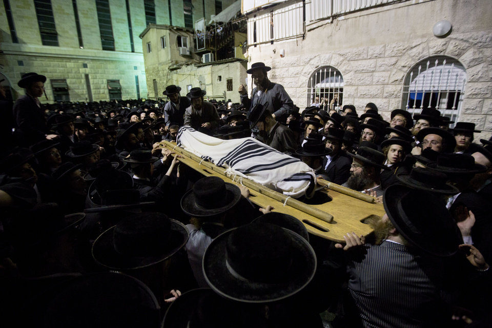 Photo - An ultra-Orthodox Jewish man carries the body of Avrohom Wallis during his funeral in Jerusalem, Monday, Aug. 4, 2014. An assault carried out with a construction vehicle served as another reminder of the tense climate. Israeli TV stations broadcast a series of amateur videos of the attack, in which a Palestinian man used the front shovel of a construction excavator to ram a bus and tip it over. Police said a man who worked at the site was run over and killed by the construction vehicle. He was identified as a 29-year-old religious inspector whose job was to ensure that ancient graves were not damaged by construction work. A policeman who happened to be in the area shot the driver, who was identified as a resident of a Palestinian neighborhood in east Jerusalem. The man's uncle, Hisham Jaabis, said the incident was a traffic accident and that his nephew had been gunned down in cold blood while trying to dodge the bus.