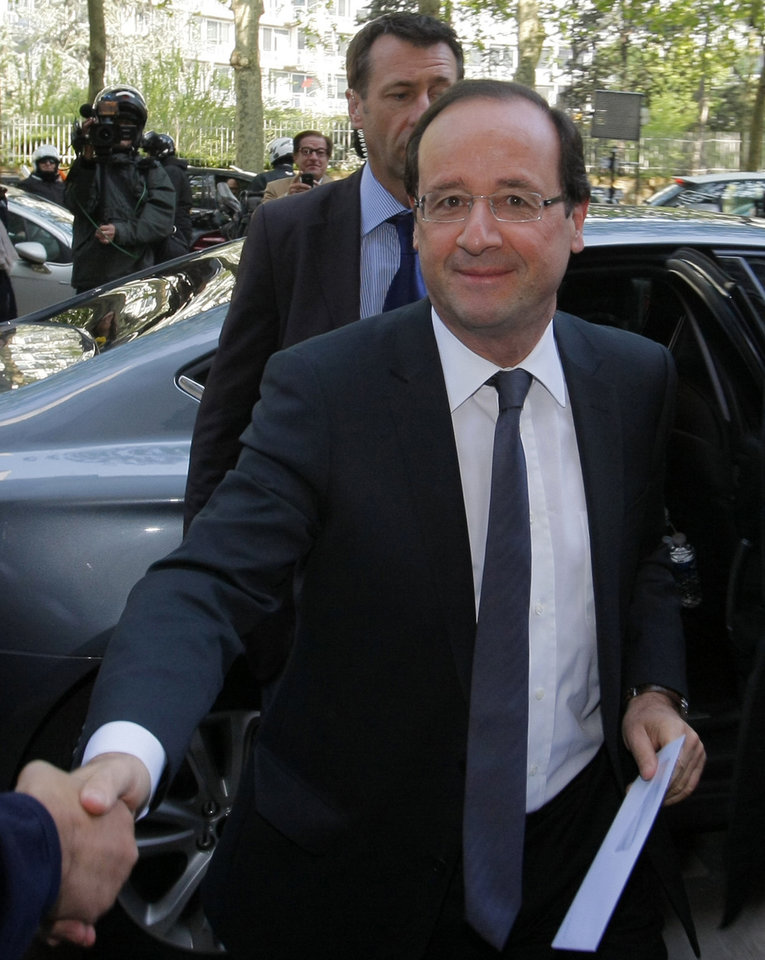 Photo -   President-elect Francois Hollande is greeted as he arrives at the Socialist Party headquarters in Paris Monday May 7, 2012. France handed the presidency to leftist Hollande, a champion of government stimulus programs who says the state should protect the downtrodden, a victory that could deal a death blow to the drive for austerity that has been the hallmark of Europe in recent years. (AP Photo/Michel Spingler)
