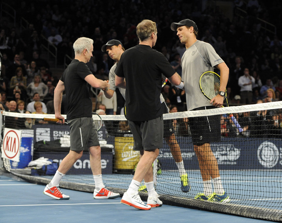 Photo - John, left, and Patrick McEnroe shake hands with Bob, second from left, and Mike Bryan after the Bryans won 8-3 in the BNP Paribas Showdown Tennis Tournament on Monday, March 3, 2014, in New York. (AP Photo/Kathy Kmonicek)