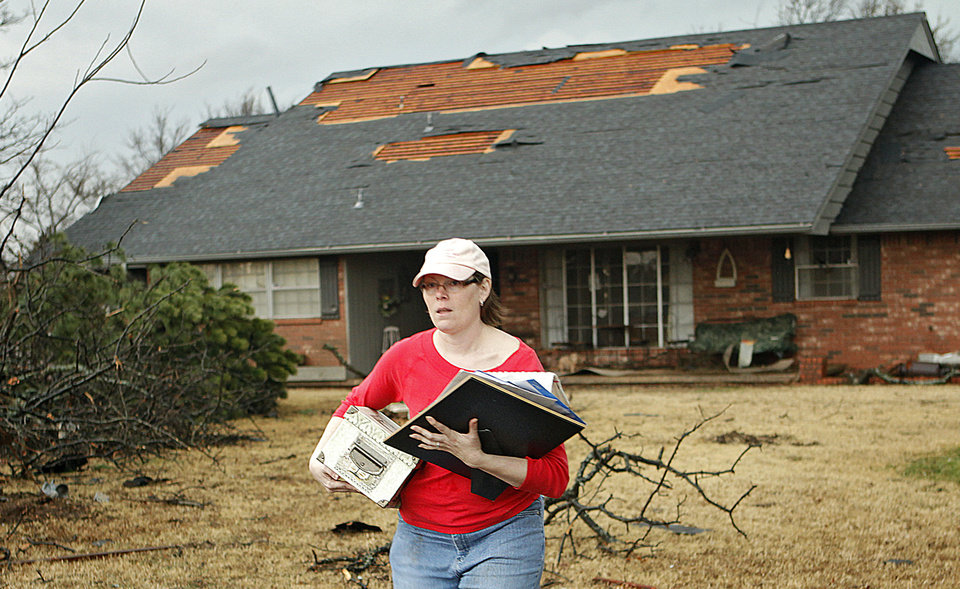 Photo - Carol Grieb carries a few items from her house at 5213 Circle Glenn that was damage by the tornado that hit north Edmond on Tuesday, Feb. 10, 2009, in Edmond, Okla.  PHOTO BY CHRIS LANDSBERGER, THE OKLAHOMAN