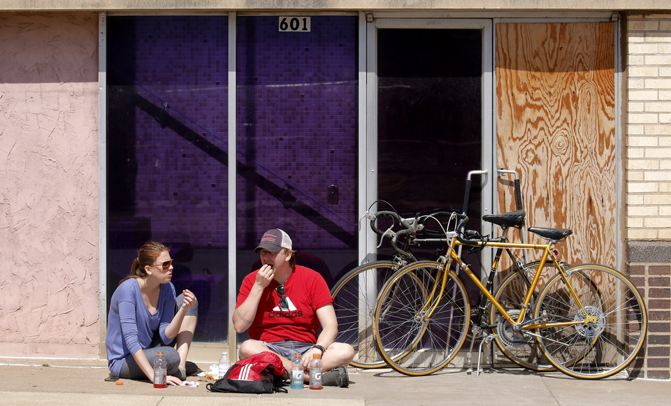 Photo - Amy Saxon and Shaun Wright sit and eat along the sidewalk at Open Streets OKC, along NW 23rd Street between Robinson and Western, Sunday, March 22, 2015. Photo by Doug Hoke, The Oklahoman