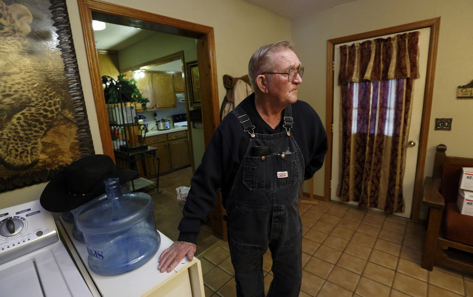 Photo - Elvin Fagan struggles with water issues at his rural home in Lexington.  He has a contract to receive drinking water in five gallon jugs like the ones on his washer. Photo by Steve Sisney, The Oklahoman  STEVE SISNEY