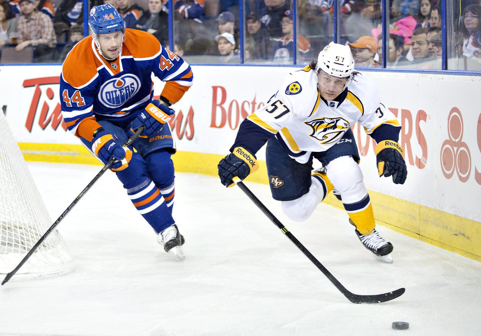 Photo - Nashville Predators Gabriel Bourque (57) and Edmonton Oilers Corey Potter (44) chase the puck during first period NHL hockey action in Edmonton, Canada, Sunday, Jan. 26, 2014. (AP Photo/The Canadian Press, Jason Franson)