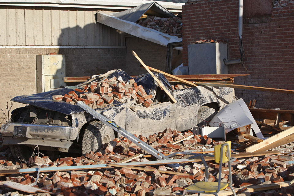 A truck is covered in rubble outside a school in Tushka, Okla., Friday, April 15, 2011 after an overnight tornado. (AP Photo/Sue Ogrocki)