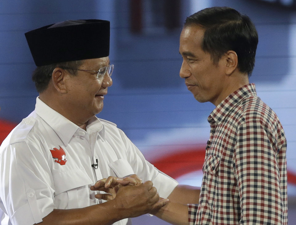 Photo - In this Saturday, July 5, 2014 photo, Indonesian presidential candidates, former special forces commander Prabowo Subianto, left, and Jakarta Governor Joko Widodo shake hands during a televised presidential candidate debate in Jakarta, Indonesia. Saturday, July 5, 2014. As the world's third-largest democracy prepares to head to the polls on Wednesday, July 9, the country remains fiercely divided as the common man and the military man slug it out in a race once considered a sure thing, but now way too close to call. (AP Photo/Dita Alangkara)