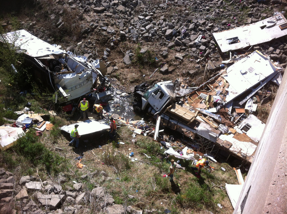 Officials work the scene of a Minnesota-bound motor home on Sunday, April 1, 2012 in a ravine off Interstate 35 in northeast Kansas. The Kansas Highway Patrol said the northbound Freightliner motor home was carrying 18 people and pulling a trailer when the driver lost control at 9 a.m. Sunday, and crashed into the ravine. Five were killed. (AP Photo/KMBC-TV)
