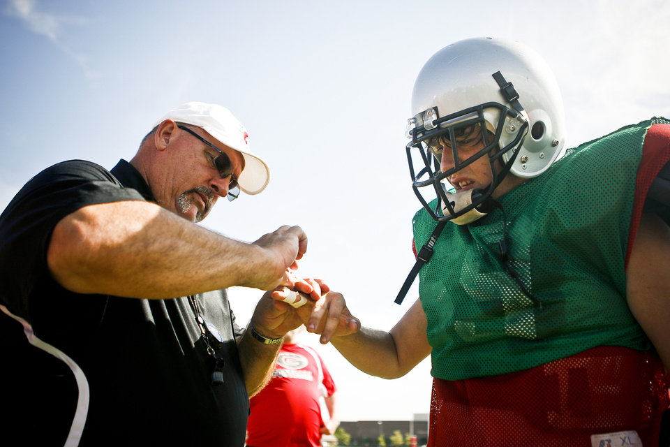 HIGH SCHOOL FOOTBALL: Generals coach Dan Burgess tapes the finger of outside linebacker Jimmy Kiplinger (69) during a scrimmage at U.S. Grant High School on Saturday, Aug. 13, 2011. Photo by Zach Gray, The Oklahoman ORG XMIT: KOD