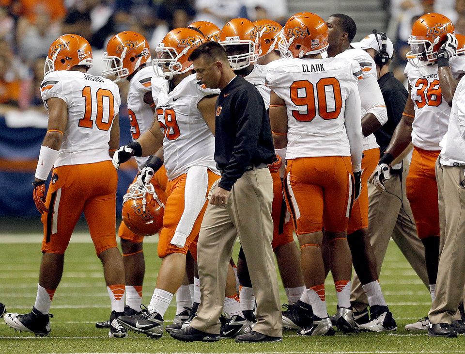 Photo - Oklahoma State head coach Mike Gundy walks to the sidelines after a time out during the first half of a college football game between the University of Texas at San Antonio Roadrunners (UTSA) and the Oklahoma State University Cowboys (OSU) at the Alamodome in San Antonio, Saturday, Sept. 7, 2013.  Photo by Sarah Phipps, The Oklahoman