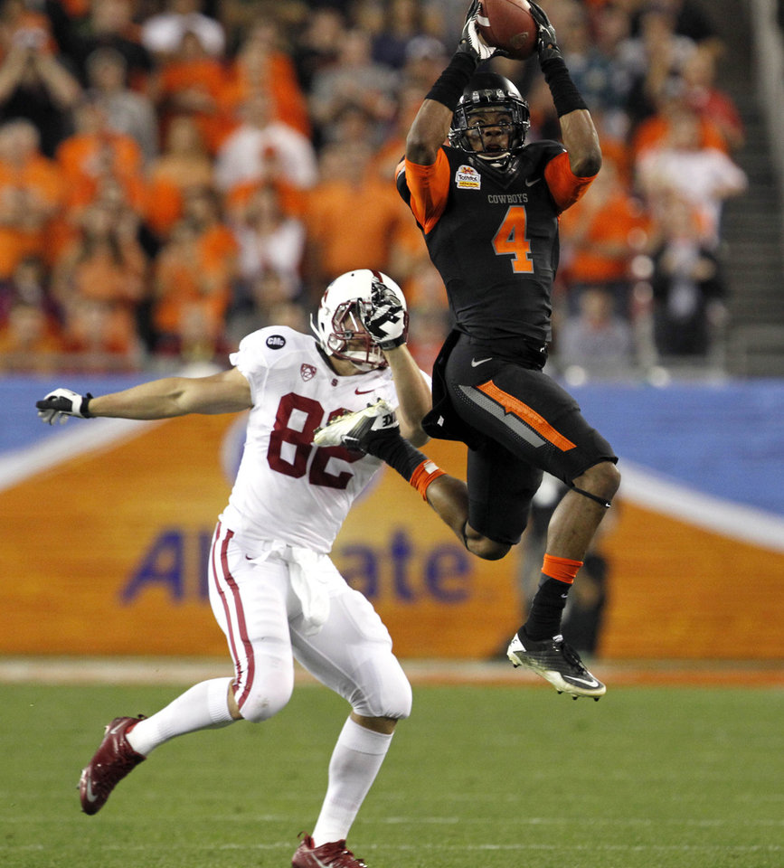 Photo - Oklahoma State cornerback Justin Gilbert (4) intercepts a pass intended for Stanford tight end Coby Fleener (82) during the first half of the Fiesta Bowl NCAA college football game Monday, Jan. 2, 2012, in Glendale, Ariz. (AP Photo/Ross D. Franklin)