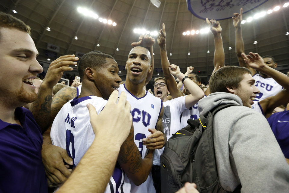Photo - TCU guard Charles Hill Jr. (0), forward Garlon Green (33) and  forward Connell Crossland (2) celebrate with the fans on the court after an NCAA college basketball game against Kansas on Wednesday, Feb. 6, 2013, in Fort Worth, Texas. TCU won 62-55. (AP Photo/Sharon Ellman)