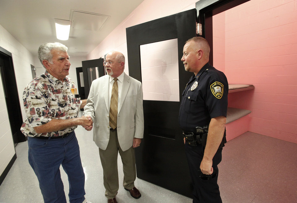 Photo - Police Chief Phil Taylor, center,  greets a visitor who is taking the open house tour of Del City's new police station.  Officer at right is Sgt. Loyd Berger.  The new police station in Del City was officially dedicated Thursday afternoon.  Jim Beckel - THE OKLAHOMAN