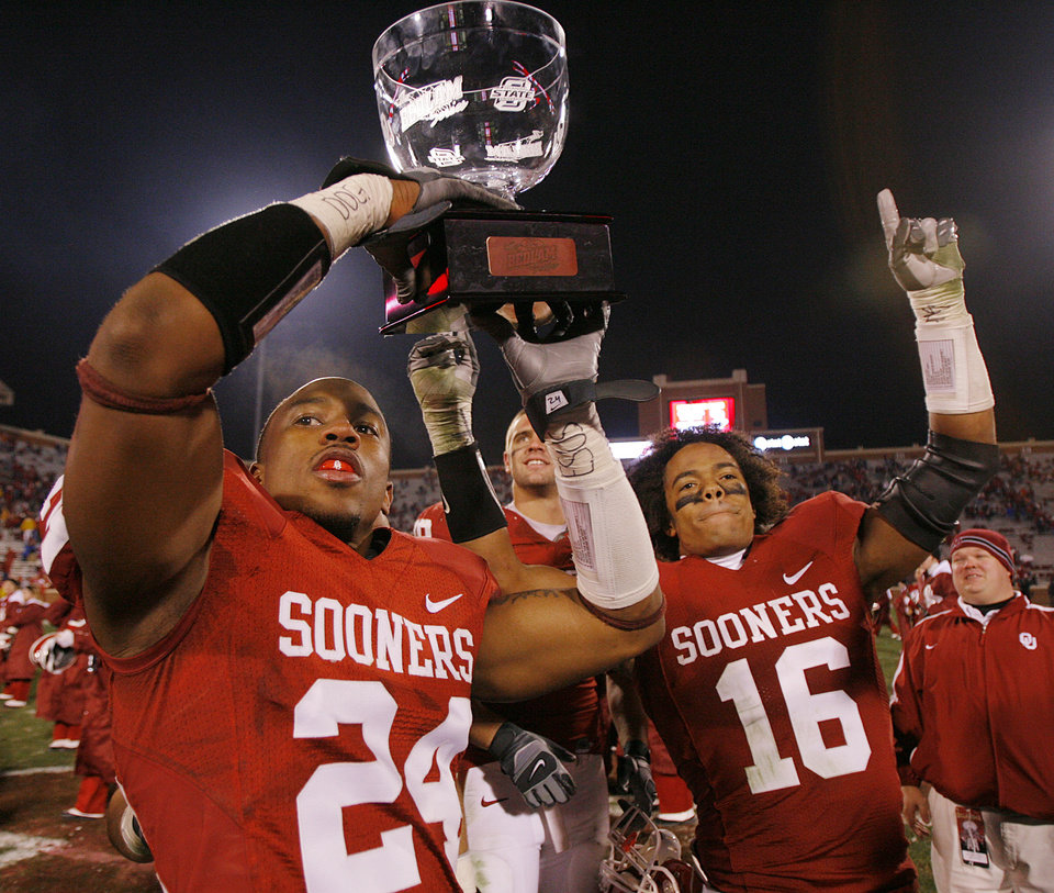 Photo - Oklahoma's Marcus Walker (24) and Lewis Baker (16) celebrate with the Bedlam Trophy after the 49-17 win over Oklahoma State in the college football game between the University of Oklahoma Sooners (OU) and the Oklahoma State University Cowboys (OSU) at the Gaylord Family-Memorial Stadium on Saturday, Nov. 24, 2007, in Norman, Okla. 