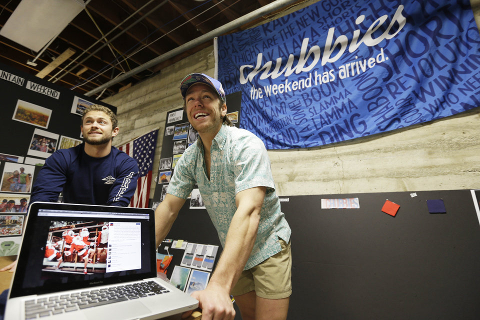 Photo - In this photo taken Wednesday, Dec. 4, 2013, co-founders Tom Montgomery, left, and Preston Rutherford, right, stand behind a laptop showing an Instagram from a holiday photo shoot at the headquarters of Chubbies Shorts in San Francisco.  Chubbies uses Facebook for marketing tools like videos that users will share with their friends. It uses Twitter for conversations with customers, and posts photos on Instagram to create buzz about their products. (AP Photo/Eric Risberg)