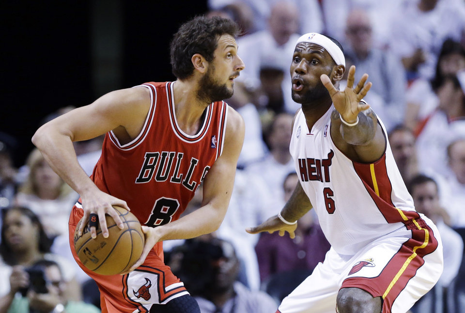 Photo - Chicago Bulls guard Marco Belinelli (8), of Italy, looks for an open teammate past Miami Heat forward LeBron James (6) during the first half of Game 2 of their NBA basketball playoff series in the Eastern Conference semifinals, Wednesday, May 8, 2013, in Miami. (AP Photo/Lynne Sladky)