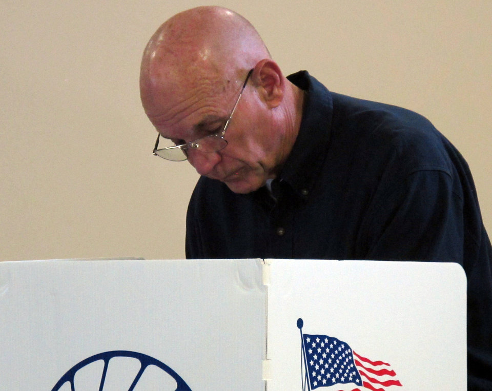 Republican state Senate candidate Dick Barta fills out his ballot at his home polling place at the Sunrise Optimist Activities center, Tuesday, Nov. 6, 2012, in Topeka, Kan. Barta is a former Shawnee County sheriff who's trying to unseat Democratic state Sen. Laura Kelly of Topeka. (AP Photo/John Hanna)