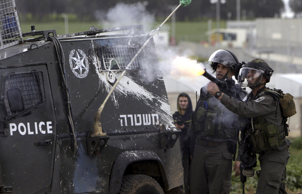 An Israeli border policeman fires tear gas during a protest north of the West Bank city of Jenin in support to the Palestinian prisoners Friday, Feb. 22, 2013.  Israel holds a few thousand Palestinians on charges ranging from rock throwing to deadly attacks.  (AP Photo/Mohammed Ballas)
