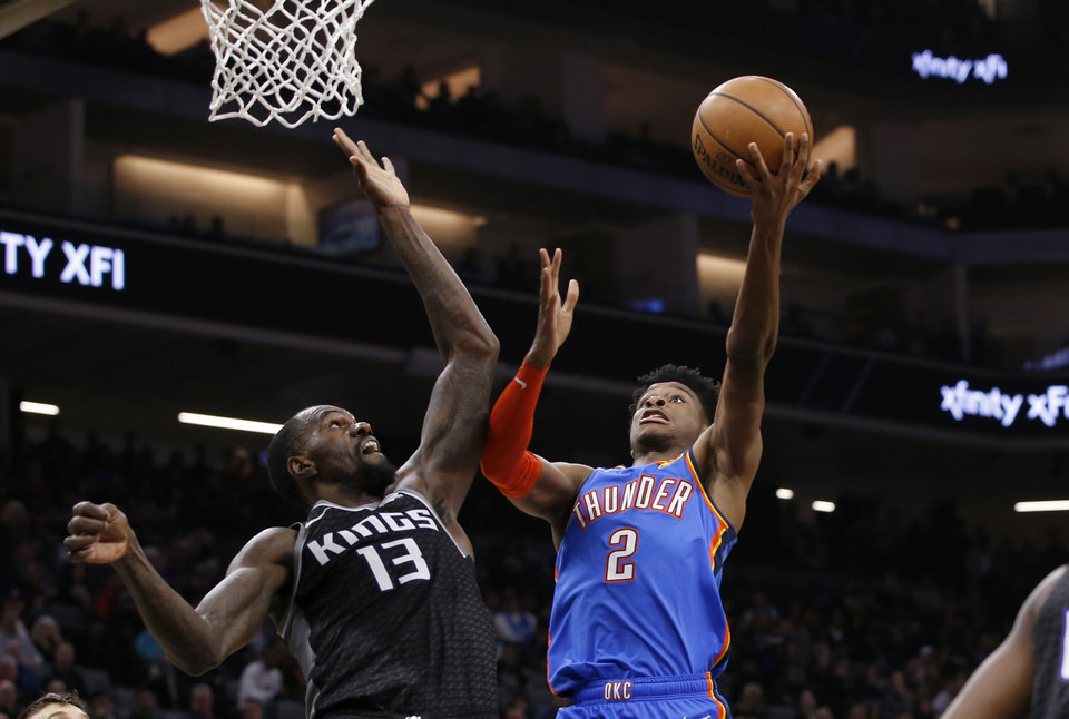Photo - Oklahoma City Thunder guard Shai Gilgeous-Alexander, right, goes to the basket against Sacramento Kings center Dewayne Dedmon, left, during the first quarter of an NBA basketball game in Sacramento, Calif., Wednesday, Jan. 29, 2020. (AP Photo/Rich Pedroncelli)