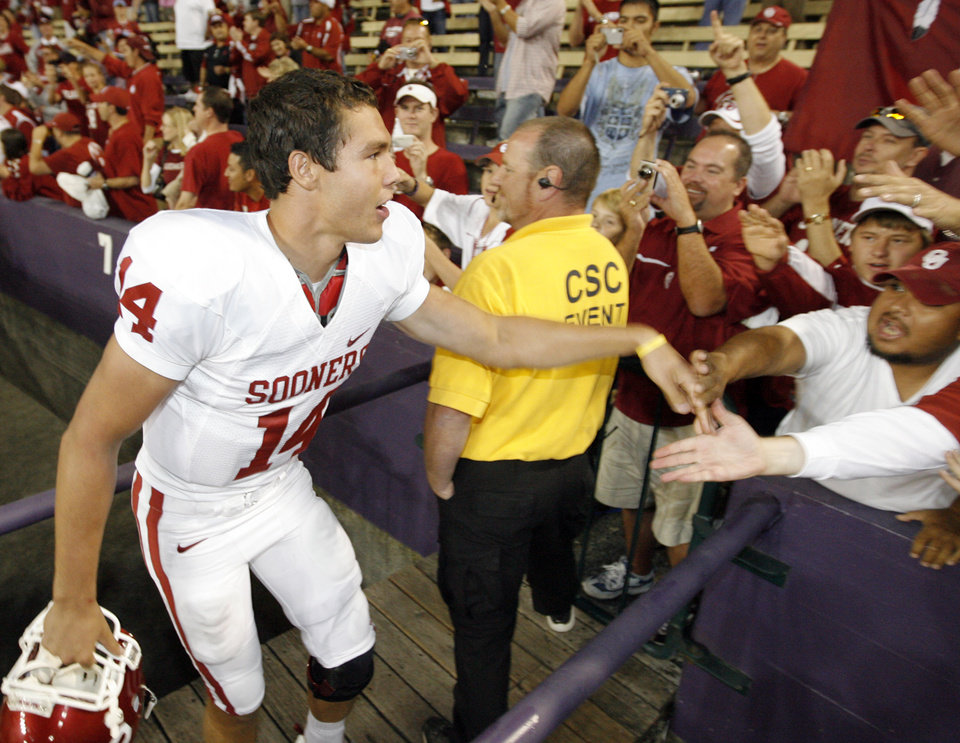 Photo - OU quarterback Sam Bradford (14) slaps hands with OU fans after the college football game between the University of Oklahoma (OU) and Washington at Husky Stadium in Seattle, Wash., Saturday, September 13, 2008. OU beat UW, 55-14. BY NATE BILLINGS, THE OKLAHOMAN ORG XMIT: KOD