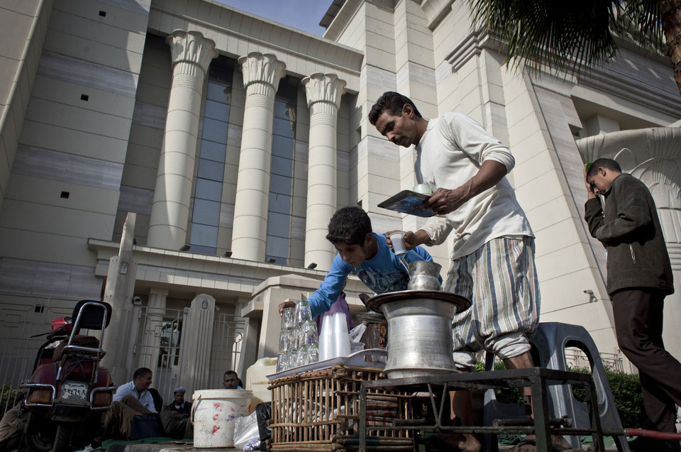 Photo - An Egyptian street vendor serves tea for supporters of Egyptian President Mohammed Morsi, unseen, during a protest in front of Egypt's top court, in Cairo, Egypt, Monday, Dec. 3, 2012. The Egyptian president's top legal adviser says the country's election commission has begun preparations for the referendum on Dec. 15 on a highly contentious draft constitution. (AP Photo/Nasser Nasser)
