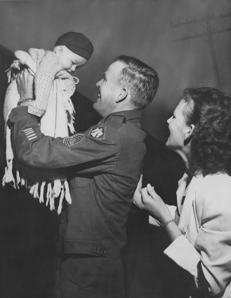 Photo - Returning Thunderbirds Meets Son for First Time.  M-Sgt. Ray Mathis, Hollis, gets his first look at 6 month old Charles Ray, born while he was overseas with the 45th division.  It was an exciting moment for the sergeant and his wife Doris.  Photographer and original date unknown.  Published in The Oklahoma City Times 04/17/1952.