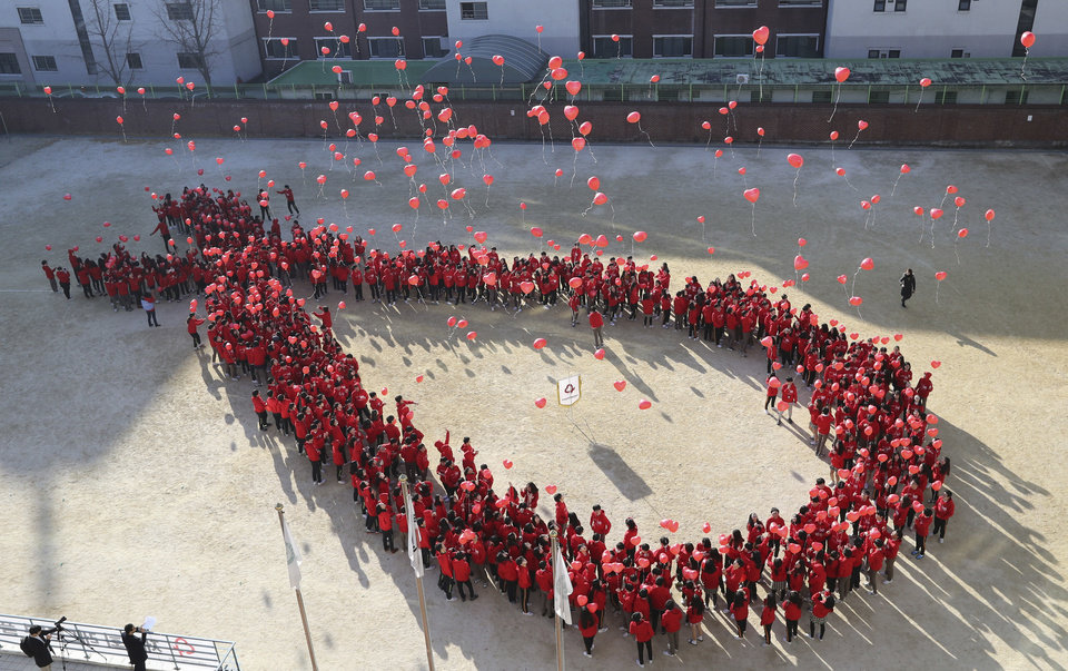 Photo - South Korean students make a formation in the shape of the red ribbon, the universal symbol of awareness and support for those living with HIV, as they release balloons during an event to mark the upcoming World AIDS Day on Dec. 1, in Seoul, South Korea, Tuesday, Nov. 29, 2016. (AP Photo/Lee Jin-man)