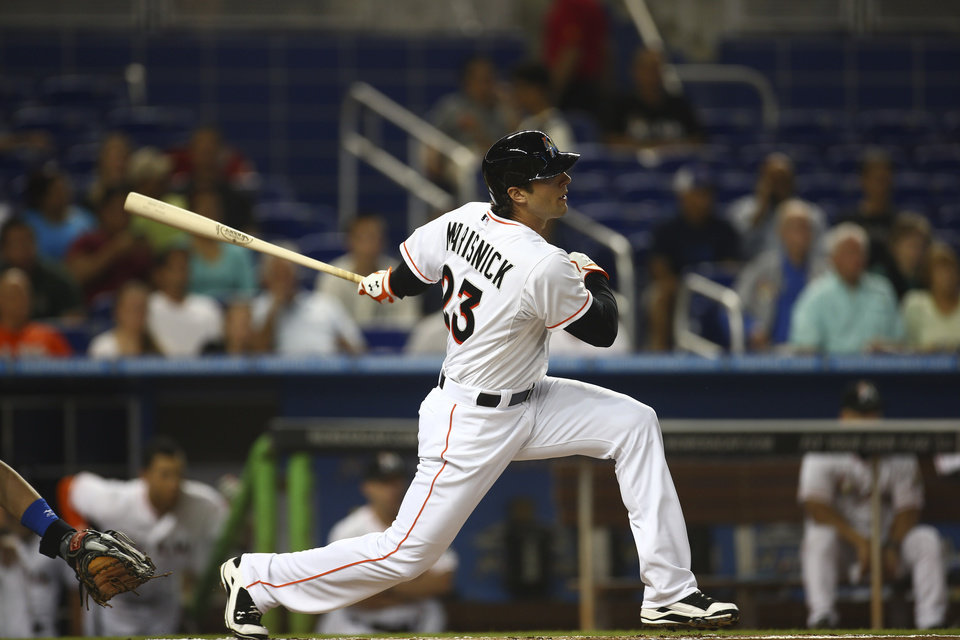 Photo - Miami Marlins' Jake Marisnick hits a single off  Chicago Cubs pitcher Jason Hammel during the first inning of a baseball game in Miami, Monday, June 16, 2014. (AP Photo/J Pat Carter)