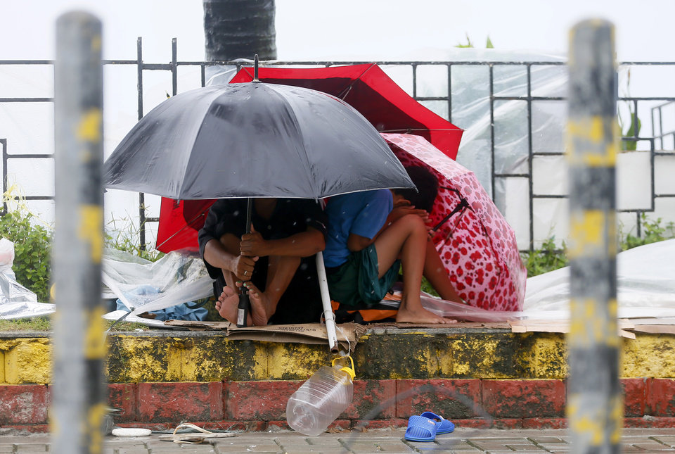 Photo - Residents huddle together under their umbrellas as strong winds and slight rain are brought by Typhoon Koppu Sunday, Oct. 18, 2015 in Manila, Philippines. The slow-moving typhoon blew ashore with fierce wind in the northeastern Philippines early Sunday, toppling trees and knocking out power and communications. Officials said there were no immediate reports of casualties. (AP Photo/Bullit Marquez)