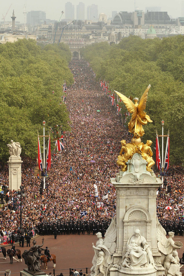 Photo - Members of the public proceed along the Mall and around the Queen Victoria Memorial as they celebrate the wedding of Britain's Prince William and his wife Kate, Duchess of Cambridge, London, Friday, April 29, 2011. (AP Photo/Oli Scarff, Pool) ORG XMIT: RWDJ144