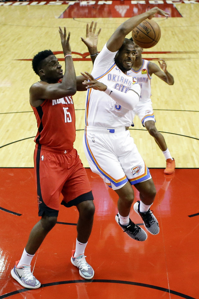 Photo - Oklahoma City Thunder guard Chris Paul, right, breaks up a pass intended for Houston Rockets center Clint Capela (15) during the first half of an NBA basketball game, Monday, Oct. 28, 2019, in Houston. (AP Photo/Eric Christian Smith)