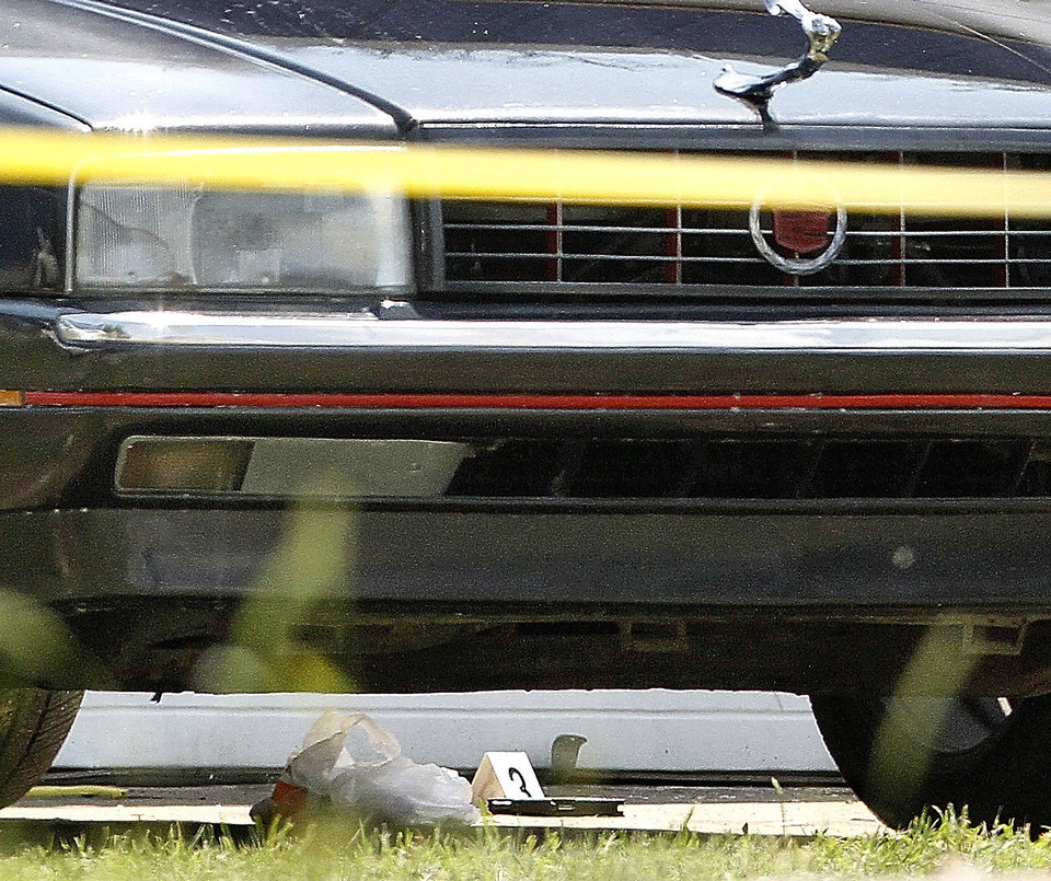 Photo - A handgun is on the concrete next to this car Monday at a crime scene in the 900 block of SW 27.  Photo by Jim Beckel, The Oklahoman