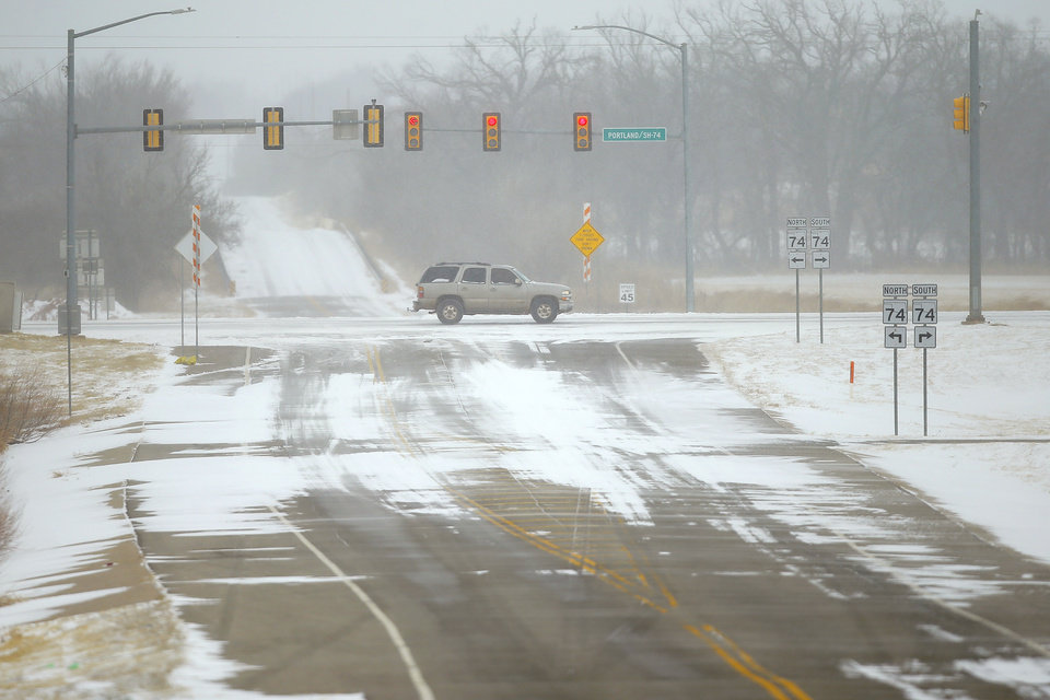 Photo - Snow blows over the intersection of Portland Avenue and Coffee Creek Road in northwest Oklahoma City during a winter storm, Sunday, Feb. 14, 2021. [Bryan Terry/The Oklahoman]
