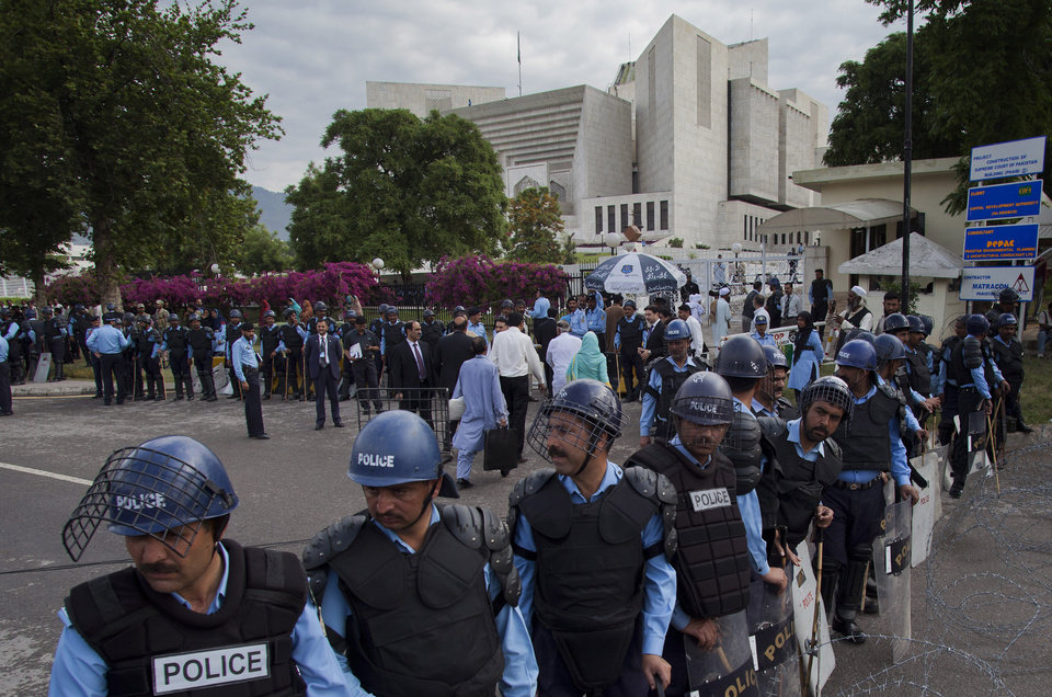 Photo -   Policemen in riot-gears cordon off the Supreme court as Pakistani Prime Minister Yousuf Raza Gilani, unseen, appears for a hearing in Islamabad, Pakistan, Thursday, April 26, 2012. The Supreme Court convicted Gilani of contempt on Thursday for refusing to reopen an old corruption case against President Asif Ali Zardari on Thursday, but spared him a prison term in a case that has stoked political tensions in the country. (AP Photo/B.K. Bangash)